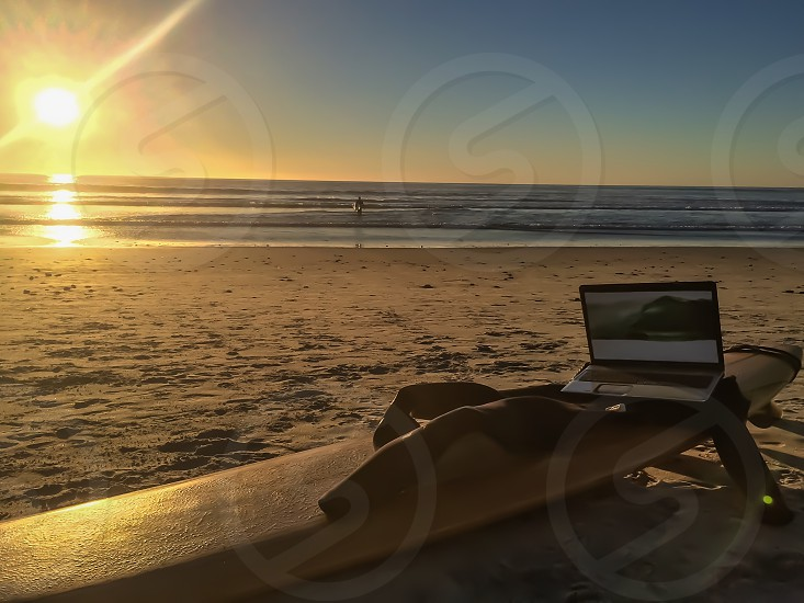 #techsavvysurfer. Open laptop computer and wetsuit sitting on surfboard on sand with ocean in the background. photo