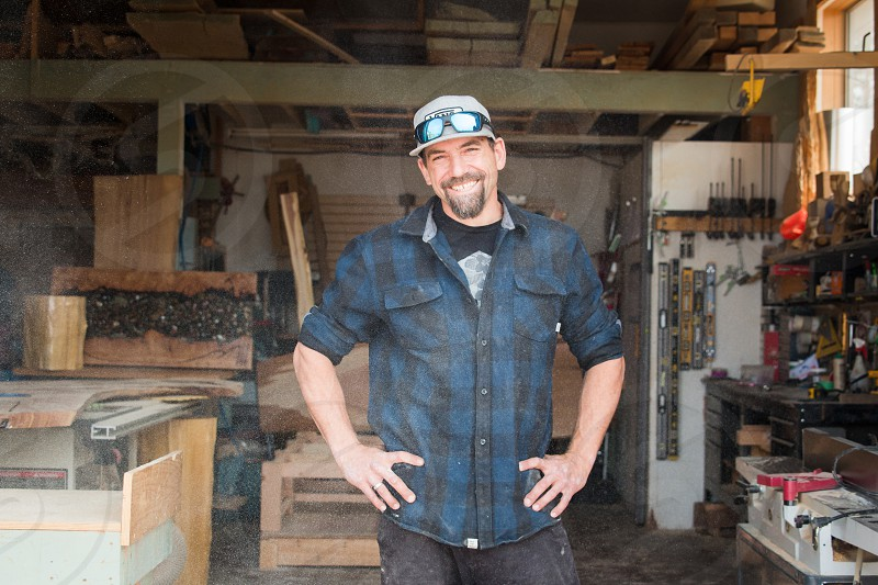 Custom wood working wearing a plaid shirt in his shop for custom lumber and cabinetry work in Canada  photo