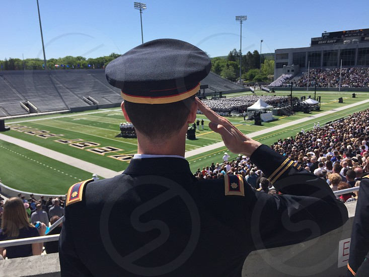 man in black uniform doing hand salute in front of crowd photo