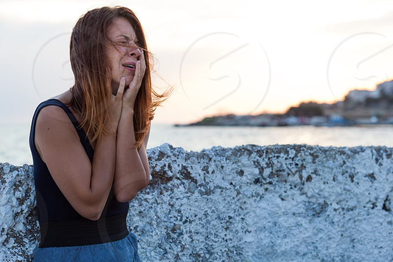 Young woman feeling sad on the pier photo