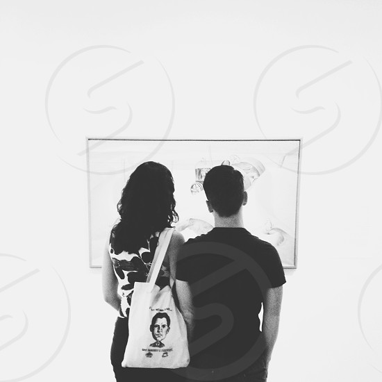 grayscale photography of couple looking at painting photo