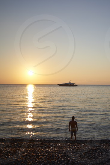 Silhouette of a young man about to go for a swim at sunrise in the ocean of the Cote D'azur in Monaco photo