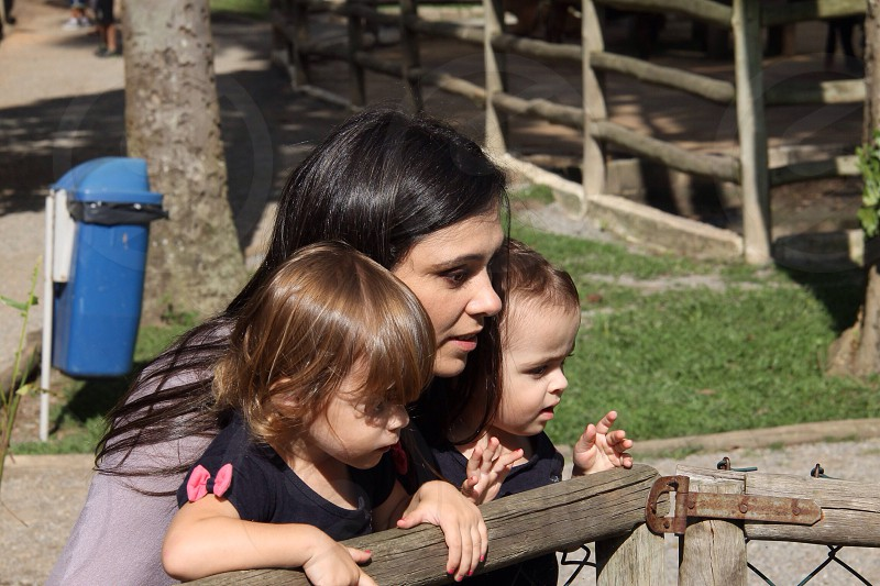woman in black with two toddlers in black near wood fence photo