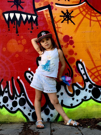 girl in white and blue tank top standing and posing against wall with graffiti art photo