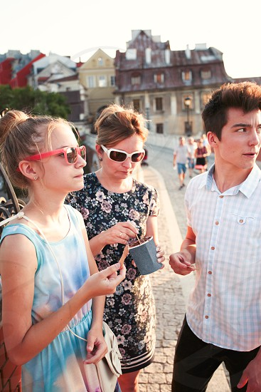 Family spending time together in the city centre enjoy eating ice cream on a summer day. Mother teenage girl and boy spending quality time on sunny afternoon eating sweet dessert. Downtown area old town in the background photo