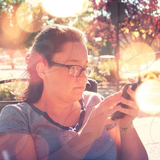 woman in black framed eyeglasses using iphone photo