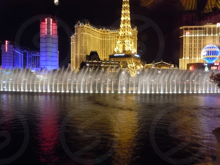 Night dancing fountain show in Las Vegas with eiffel tower at background photo