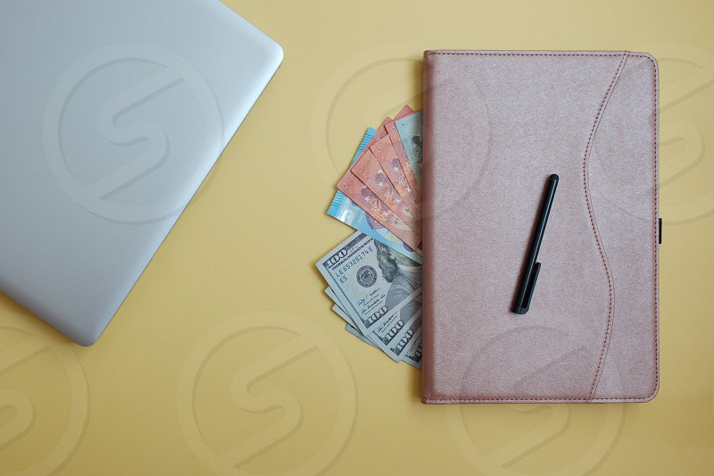 Dollar banknotes tablet and laptop against the yellow background photo