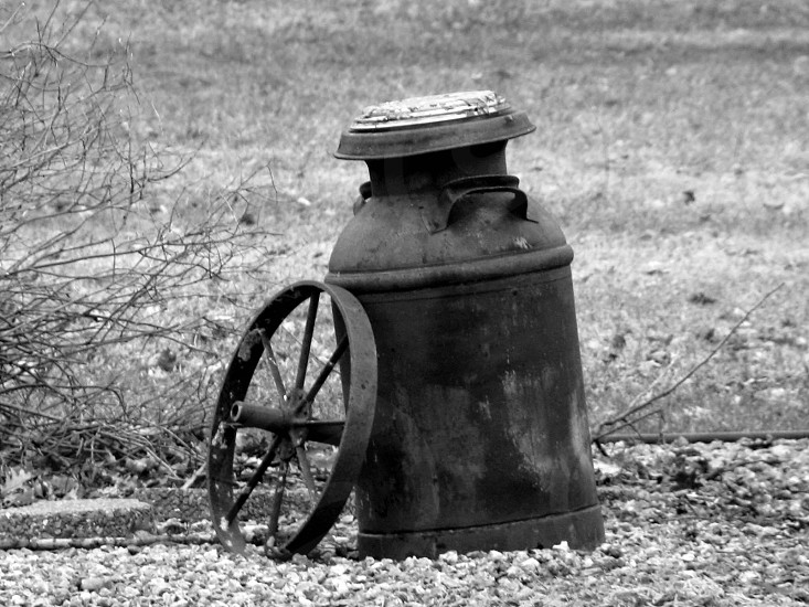 grayscale photography of milk tank besides cart wheel photo