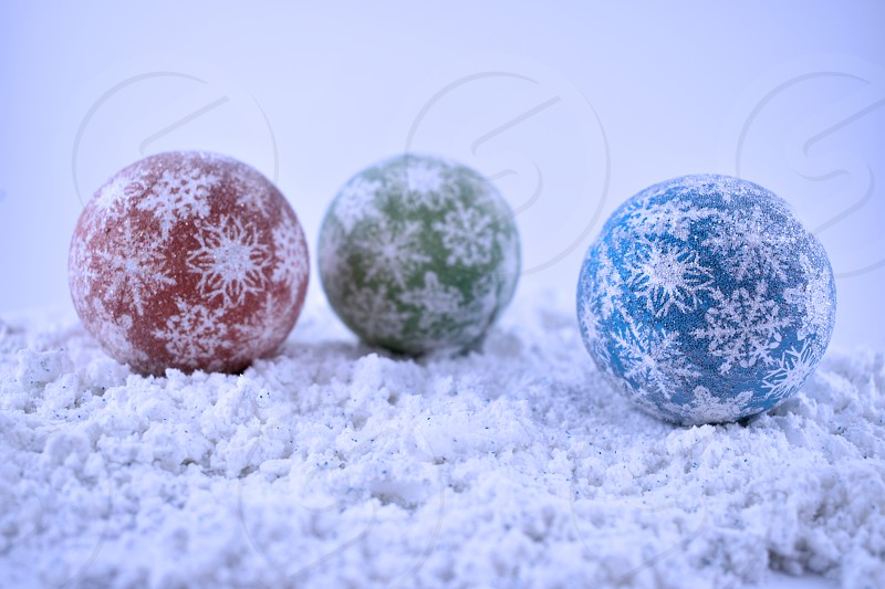 Christmas balls in the snow. Three Christmas balls isolated on snow background. Colorful Christmas balls. Christmas decoration on a blue background photo