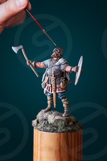 Man painting a tiny figure of Viking photo