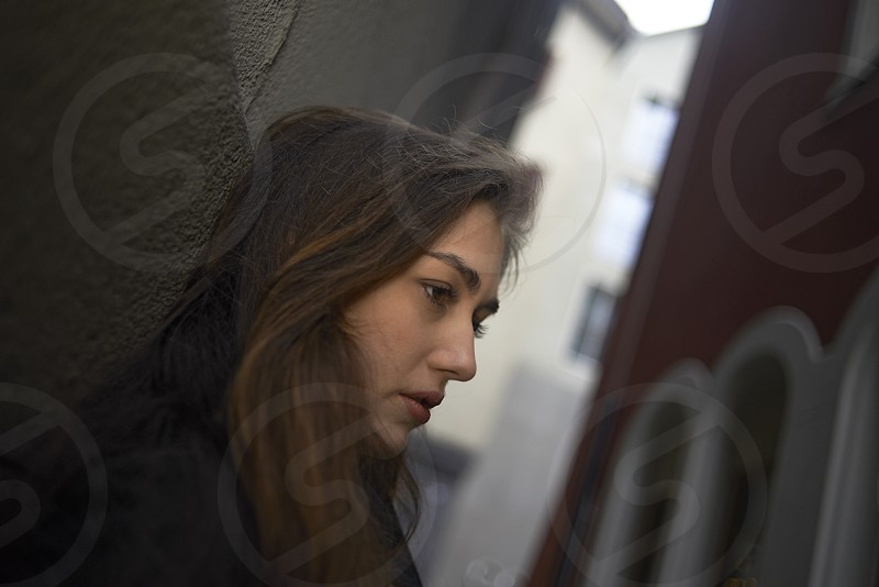 Young woman standing in an alley leaning against the wall in Zurich city centre in deep thought photo