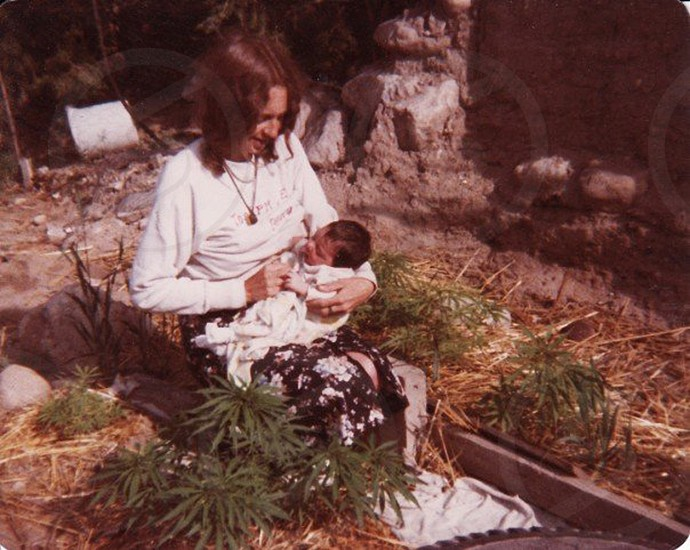 woman holding child sitting near green and brown weeds photo
