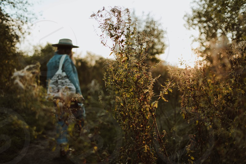 Bohemian woman walking on a nature reserve in the golden autumn evening light photo