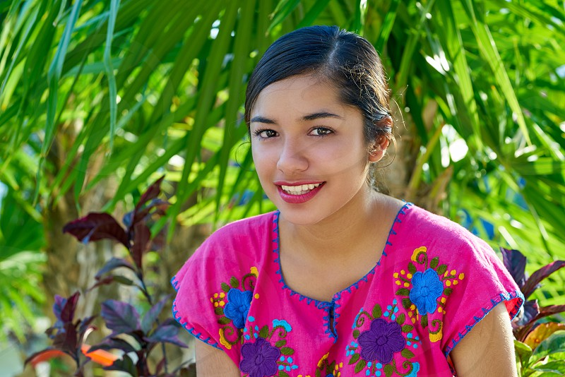 Mexican latin woman with mayan dress smiling in  the jungle photo