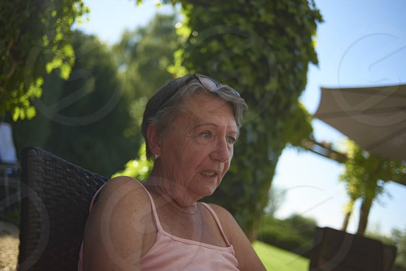 Affluent elderly woman sitting in her back garden enjoying the summer sunshine photo