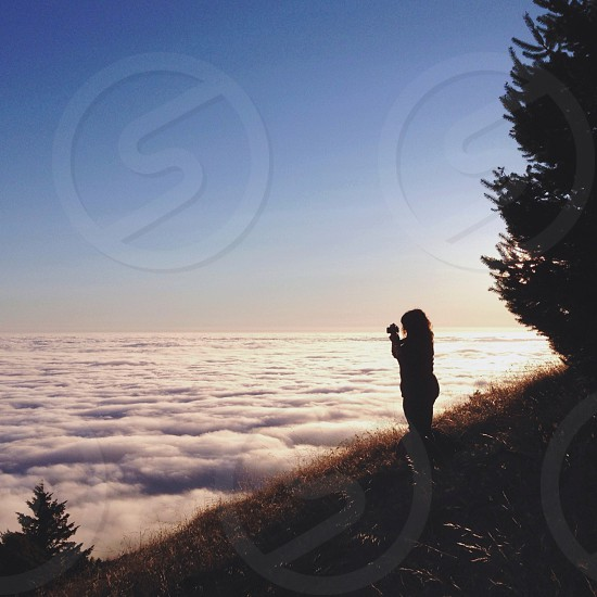 woman on top of mountain taking pictures of white clouds photo