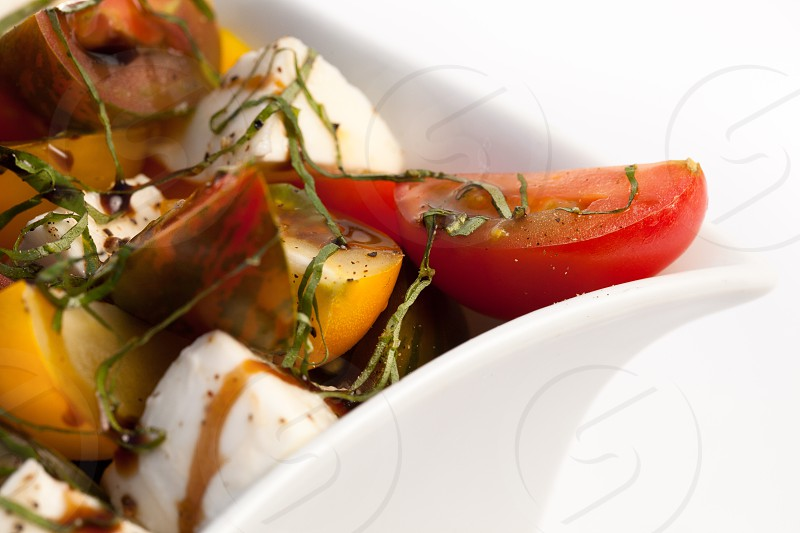 Close up detail macro shot of food against a high-key white background. Tomatoes cheese herbs dining food. photo