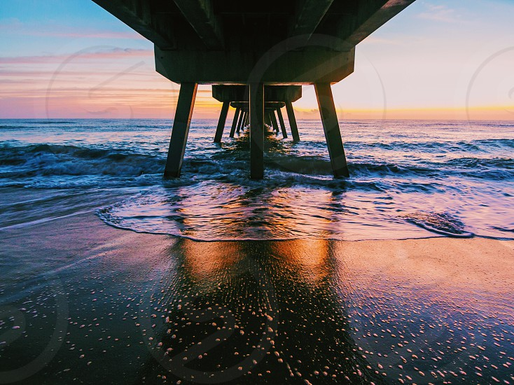 seashore under the bridge during sunset photo