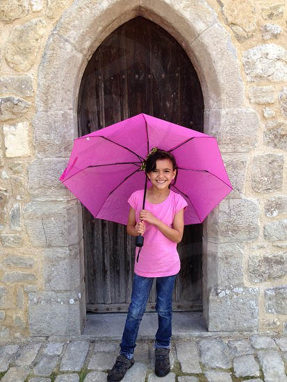Young girl pink umbrella wall punk umbrella stone wall arch photo