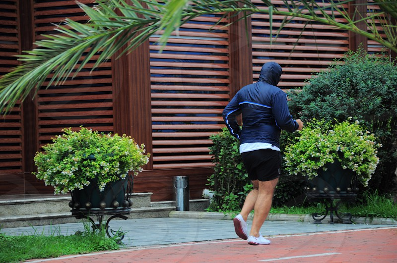 man in black jacket and shorts running on a concrete road near plant during daytime photo