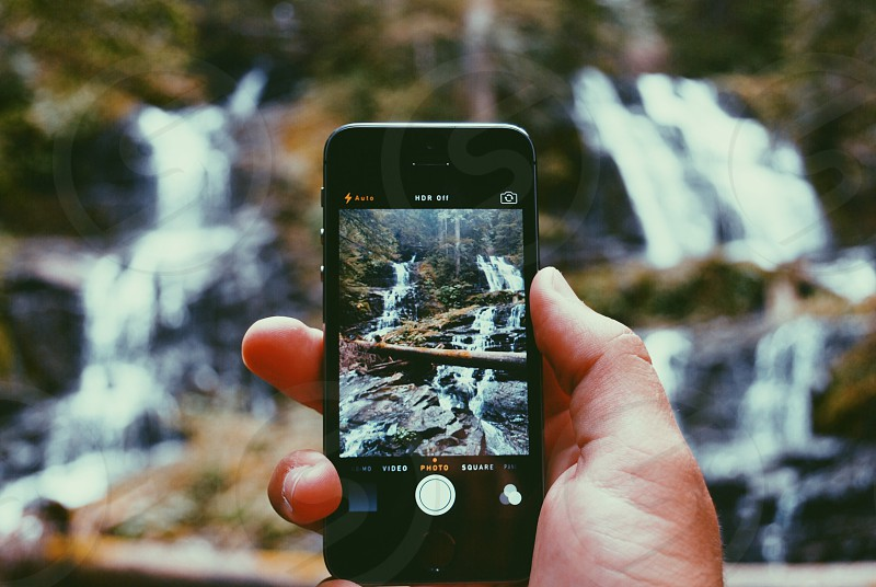 black iphone taking a photo of waterfalls photo
