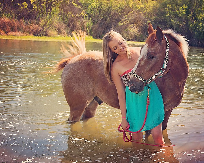close up photo of woman wearing teal and pink tube dress beside horse photo