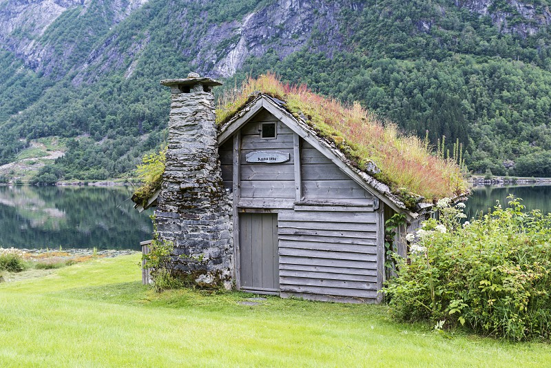 old fairytale-like house of wood with chimney of stacked slate and a roof with planting and trees on a fjord in Norway with garden with red flowers and green plants near Balestrand photo