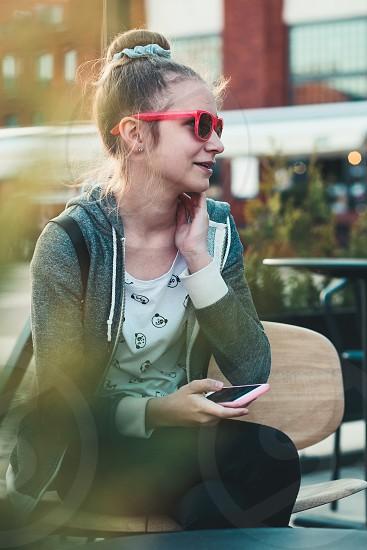 Teenage girl having fun using smartphone sitting in center of town photo