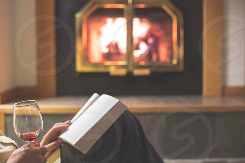 A man drinking red wine and reading a book in front of a fire photo