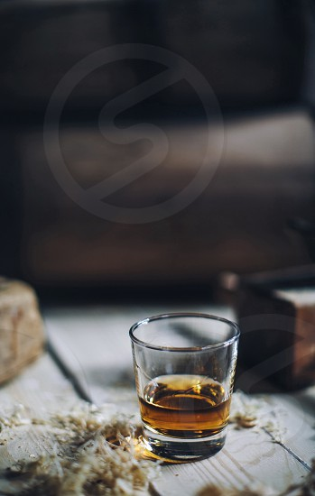 Glass of whiskey and wood barrels photo