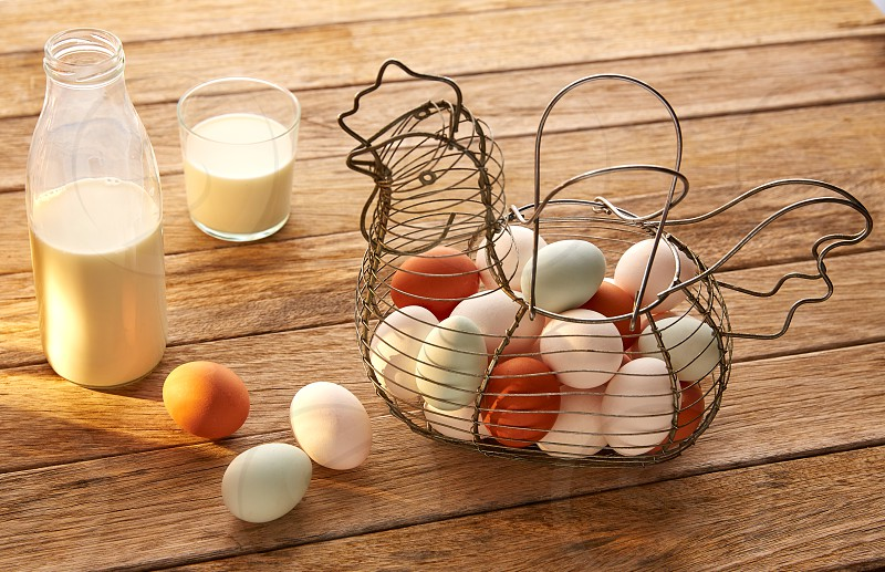 Eggs and milk in a vintage hen shape basket on wood with blue easter white and brown photo