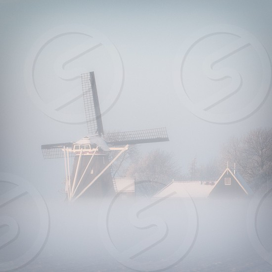 smock ground sailer wind mill near buildings and trees below gloomy sky during daytime photo