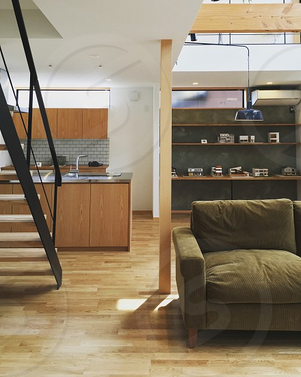 room with green fabric sofa black white wooden staircase brown parquet flooring brown wooden counter top and white painted ceiling photo