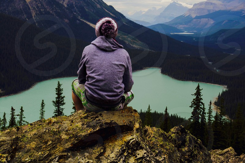 person in purple hoodie sitting on cliff facing body of water photo