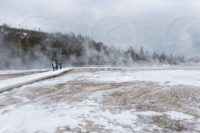 Tourists snowshoeing through the geyser area of Yellowstone National Park.  As seen on a tour from West Yellowstone Montana photo