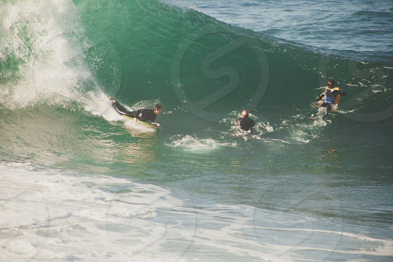 people surfing on blue sea during daytime photo