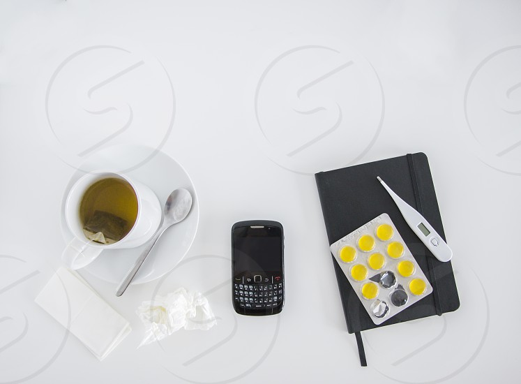 Top view of a workspace with mobile and elements of being sick photo