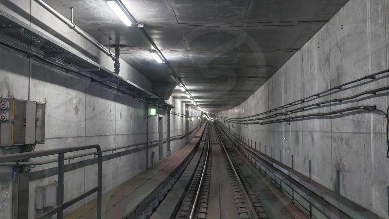 Subway rails in tunnel with wires on cement walls photo