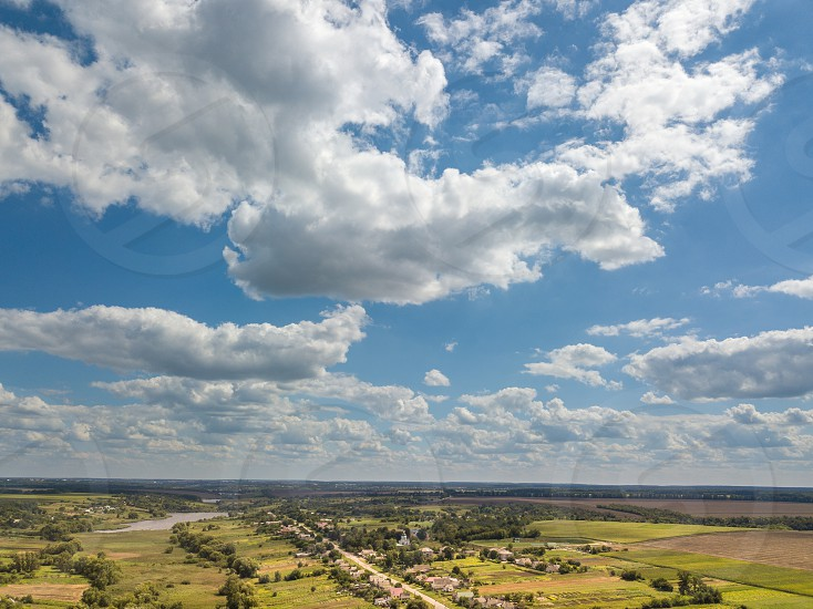 Aerial view frome drone. Bird's eye view to a rural landscape with farmlands river villages on a background blue cloudy sky in a sunny day. photo