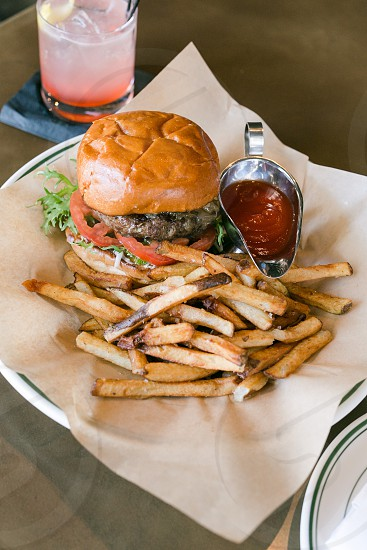 hamburger and fries with ketchup under white plate photo