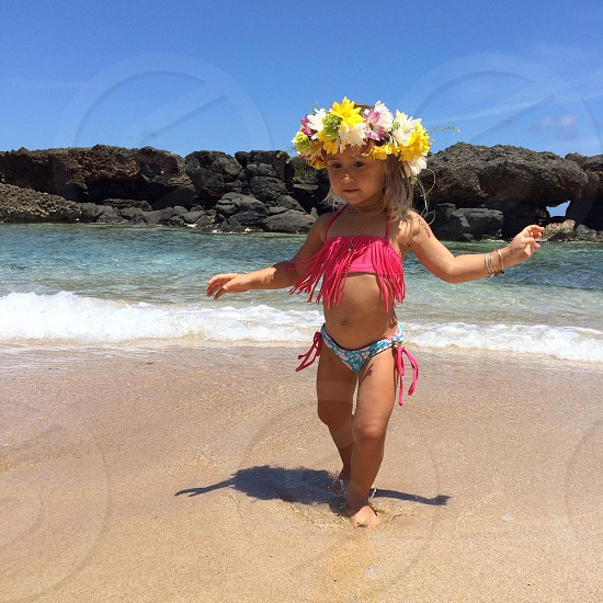 girl wearing a pink fringe bikini top and a flower crown standing on the shore of a beach photo