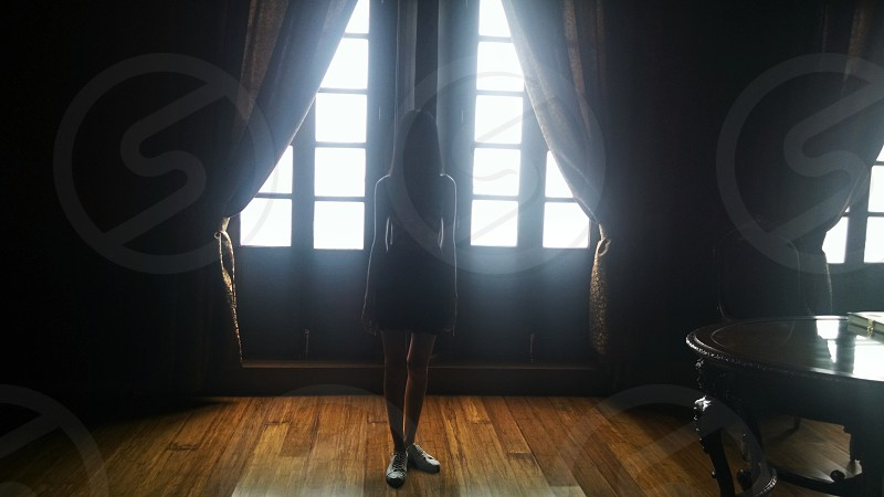 silhouette of woman standing in front of window with brown curtains photo