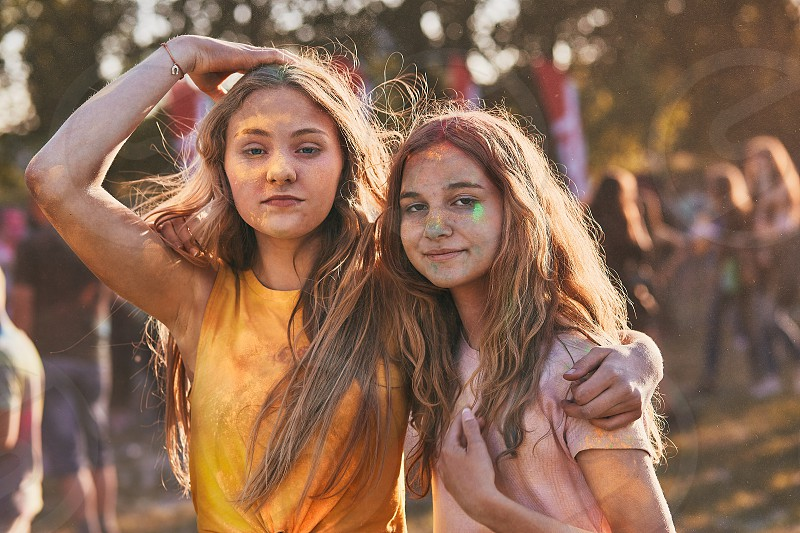 Portrait of happy smiling young girls with colourful paints on faces and clothes. Two friends spending time on holi color festival photo