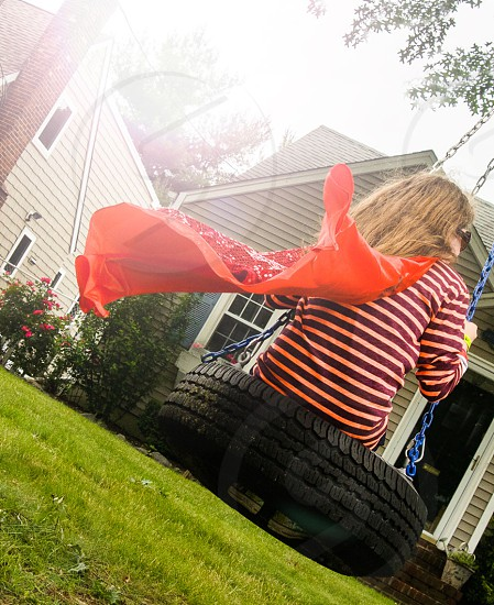 girl on the tire swing with red cape photo
