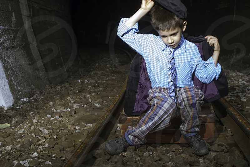 Child in vintage clothes sits on railway road in front of a tunnel. photo