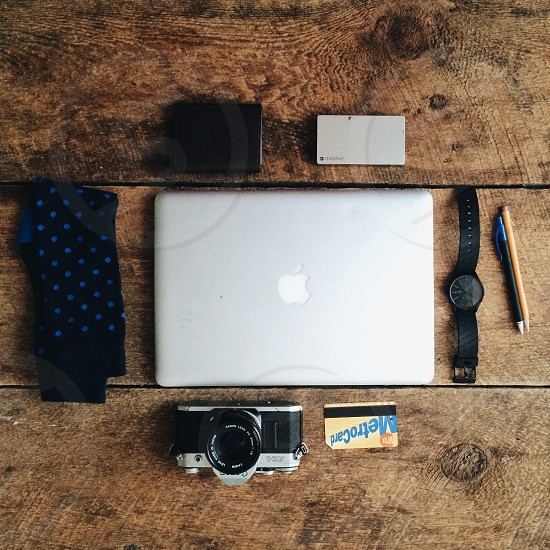 silver macbook beside black round analog watch grey and black camera and yellow and blue magnetic card photo