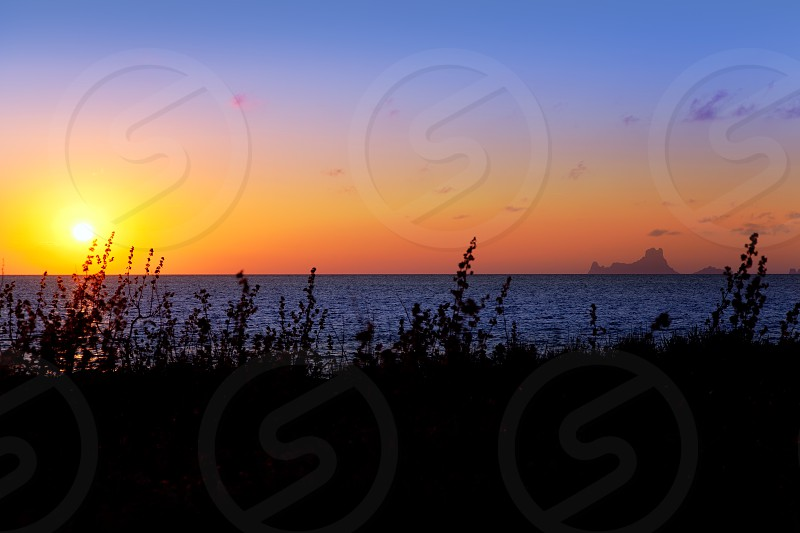 Balearic sunset from La Savina in Formentera with Es Vedra of Ibiza in background photo