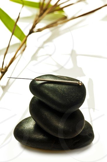 acupuncture needle on stone pyramid with bamboo photo