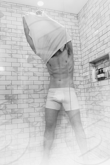 Muscular male model in steamy shower pulling white shirt off no face. photo